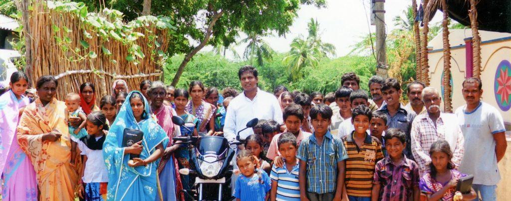 Ein junger indischer Priester freut sich über ein neues Moped für seine Arbeit