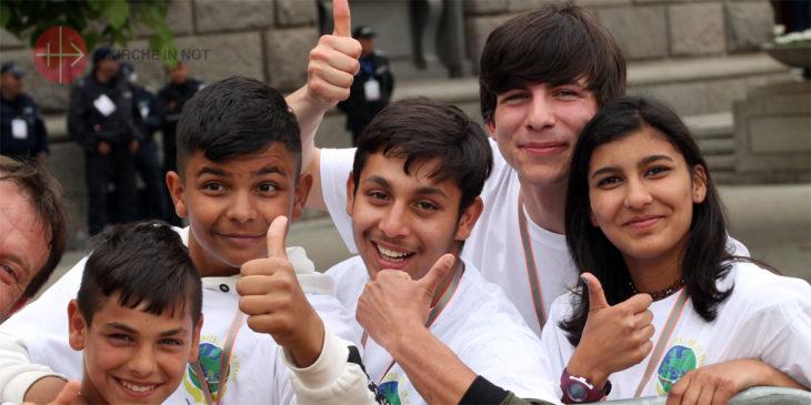 Junge Erwachsene erwarten gut gelaunt den Papst am Straßenrand in Sofia.