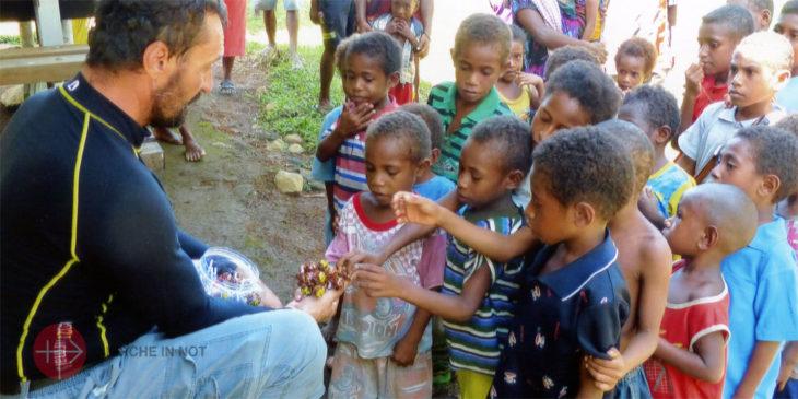Pfarrer Dariusz Wozniak verteilt Süßigkeiten an Kinder in seiner Pfarrei.